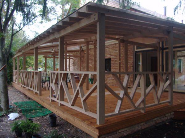 Деревянная крытая терраса у загородного дома.