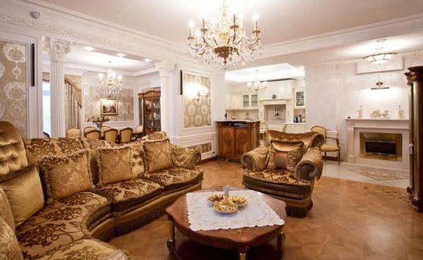 Дорогая обивка мягкой мебели, перекликающаяся с панелями, подчеркивает нарочитую роскошь классического стиля.