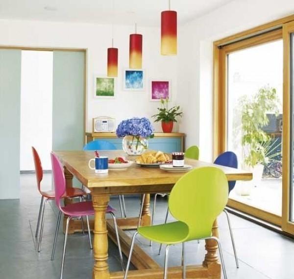 Достаточно поставить вокруг простого стола яркие разноцветные стулья, и кухня «оживет»