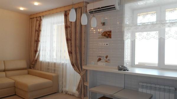 Два окна в кухне-гостиной с разным оформлением, подчеркивающим разделение на зоны
