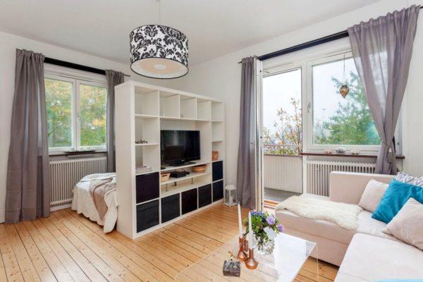 Если нет полноценной спальни, можно сделать просто нишу с кроватью при помощи стеллажа-перегородки