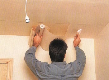 Удаление пузырьков воздуха при оклейке потолка