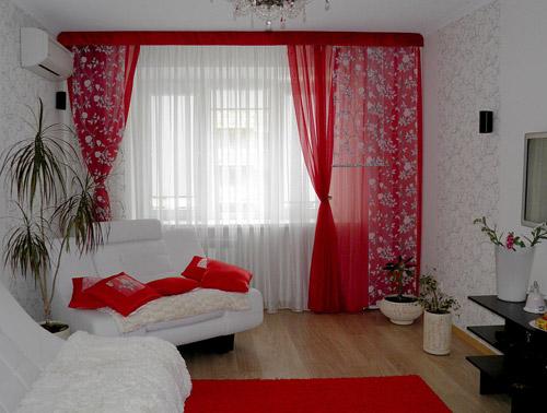 Красные шторы в сочетании с подушками и ковром того же цвета сделали однотонную гостиную праздничной и яркой