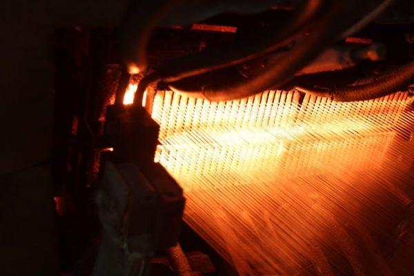 На фото показана работа экструдера, который делит расплавленное стекло на отдельные волокна