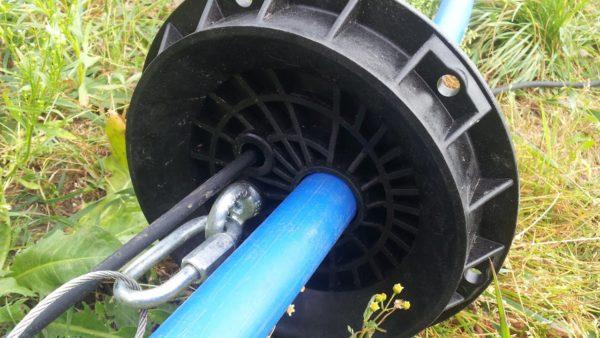 Нижняя часть оголовка с крепление троса к рым-болту и пропущенными через отверстия кабелем со шлангом