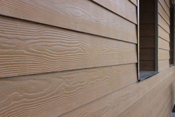 Обшитый фиброцементный сайдингом фасад внешне сложно отличить от деревянного