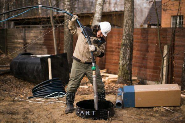 Опускаем помпу в обсадную трубу на тросе вместе со шлангом для подъема воды