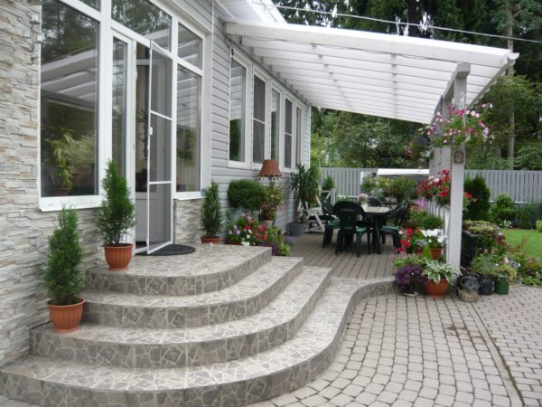 Патио возле центрального входа выгодно украшает фасад загородного дома