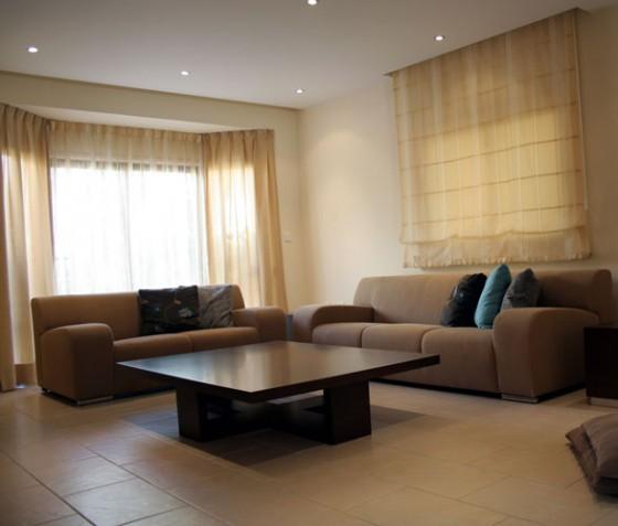 Пример разного оформления окон в интерьере гостиной в стиле минимализм