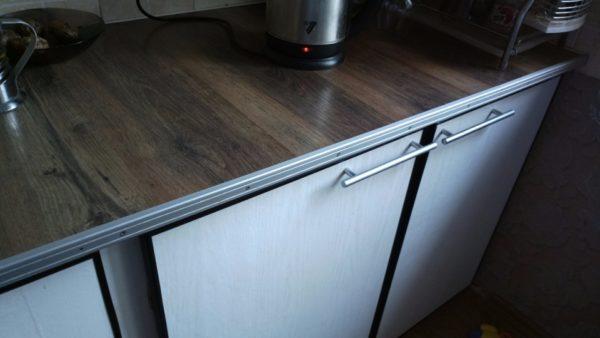 Рабочая поверхность встроенной кухни. Здесь использована та же схема, что и на рабочем столе — укладка доски на фанерную столешницу. Из-за постоянного контакта с водой швы незначительно вздулись.