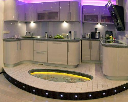 Рабочую зону в кухне-студии модно выделить при помощи оригинального подиума с подсветкой.
