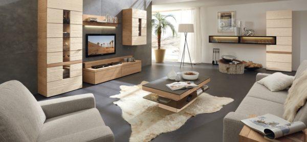 Светлая мебель в сочетании с натуральной шкурой на полу делают интерьер просторной комнаты теплее.