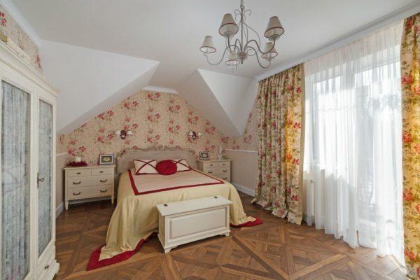В спальне власть отдали цветочному принту, оформив им стену в изголовье кровати и оконный текстиль