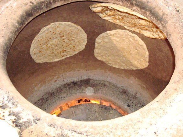 Выпекание хлеба на стенках тандыра.