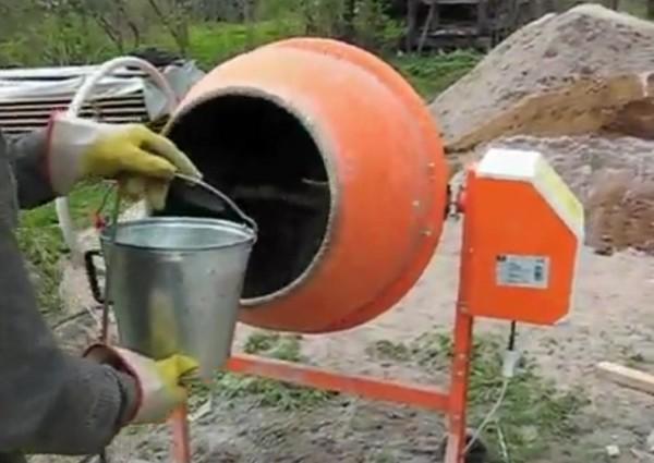 Заливаем воду в бетономешалку