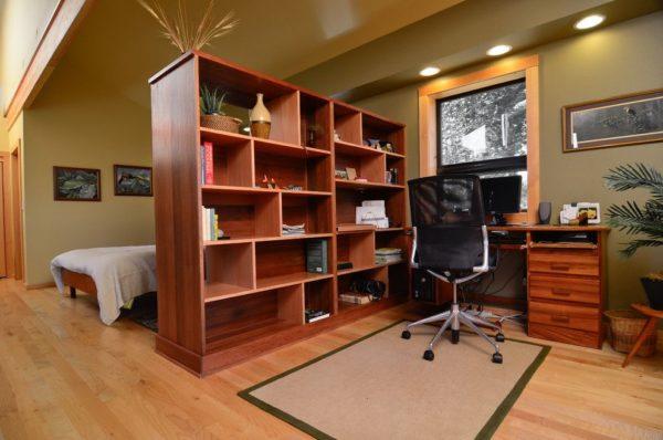 Благодаря стеллажу перегородке получается удобная рабочая область, скрытая от остальной части гостиной