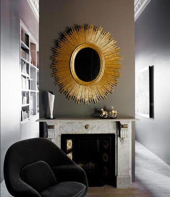 Зеркало-солнце с золотистой отделкой в сером интерьере