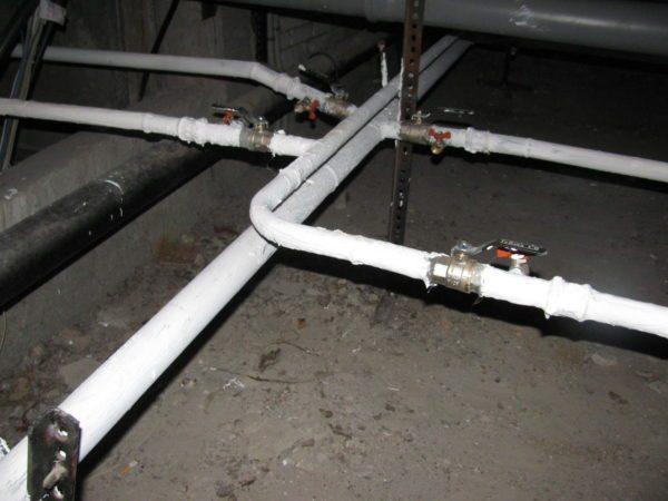 Фото окрашенной трубной разводки в подвале дома: и от холода трубы защищены, и на кожухи тратиться не пришлось
