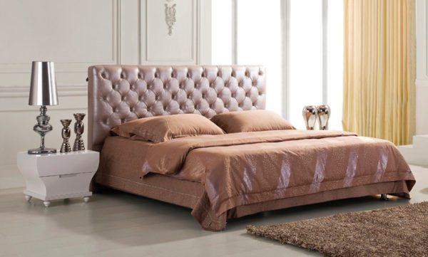Изголовье кровати из дерева с мягкой обивкой смотрится очень стильно