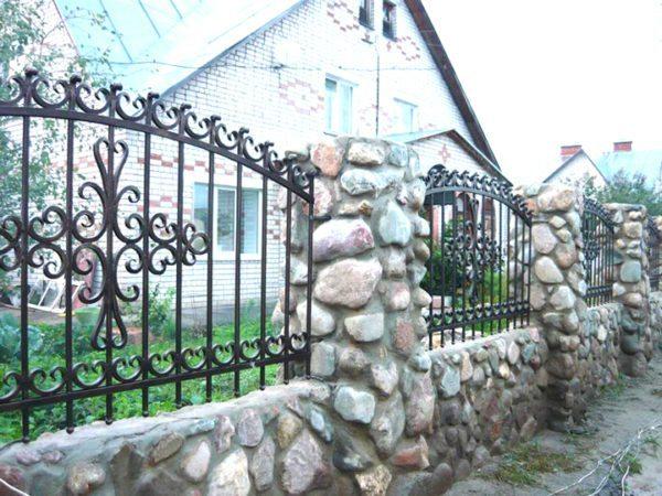 Кованые заборы для дома с каменными столбами выглядят очень аутентично