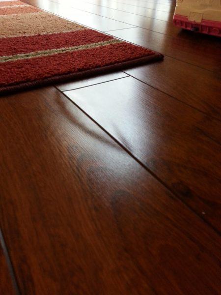 Ламинат в интерьере гостиной эффектно выглядит, но живет недолго. Первая же лужа на полу безнадежно испортит его внешний вид.