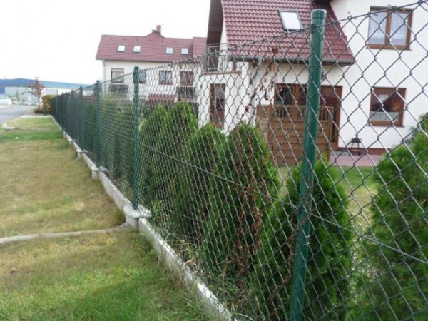 На фото: забор из рабицы – простое и практичное решение для дачных и загородных участков