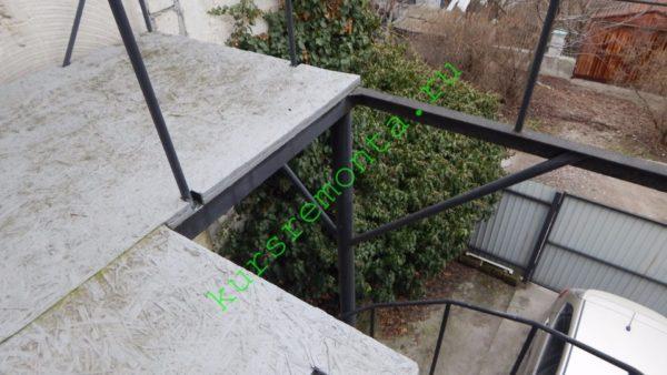 На снимке частично виден каркас балкона — стойки и балки под настил.