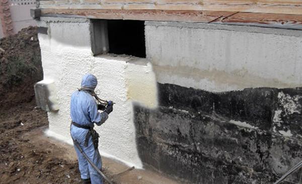 Напыление пенополиуретана на стену.