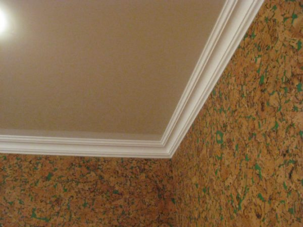 Плинтус скрывает место монтажа натяжного потолка и придает конструкции привлекательный вид