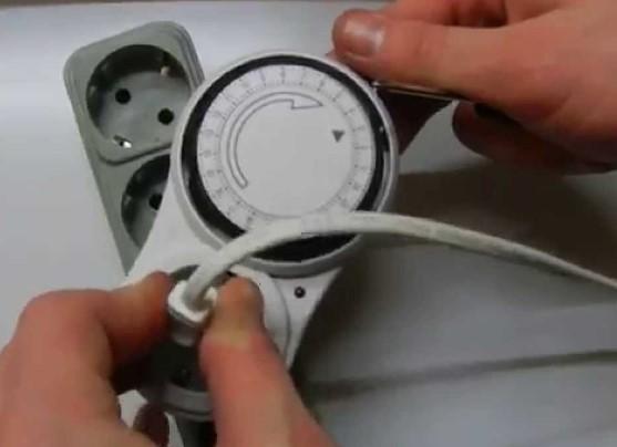 Штепсель электроприбора в посадочном месте автоматического устройства регулировки подачи электрического тока
