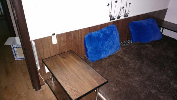 Спальня первого этажа. Из ламинированной доски изготовлены прикроватные тумбочки. Той же доской, наклеенной на силиконовый герметик, защищена стена в изголовье кровати-подиума.