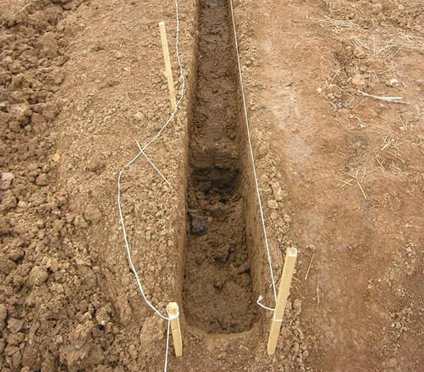 Траншея копается по натянутому шнуру, в местах расположения столбов копаются ямы глубиной 120 см