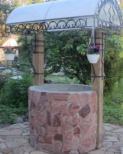 Цветник из бетонного кольца можно украсить ковкой