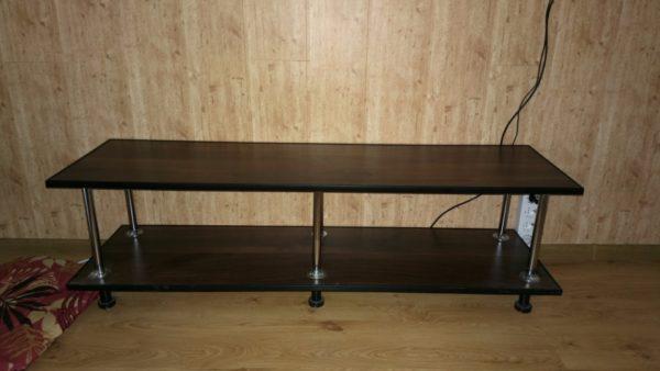 Тумба под телевизор. Материал — ламинированная доска, склеенная в два слоя, подложка к подложке. Стойки изготовлены из хромированной стальной трубы, окантовка — П-образный пластиковый профиль.