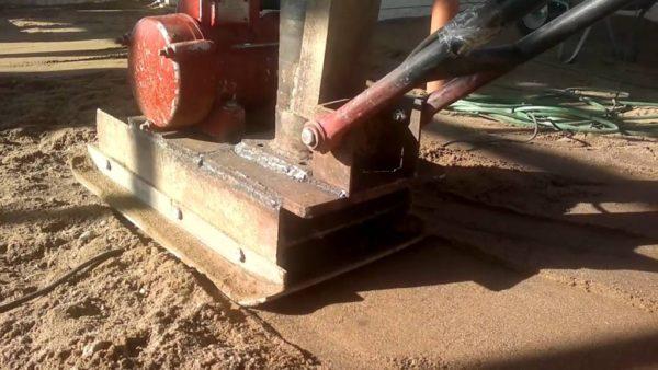 Уплотнение песчаной подсыпки перед заливкой бетонной стяжки