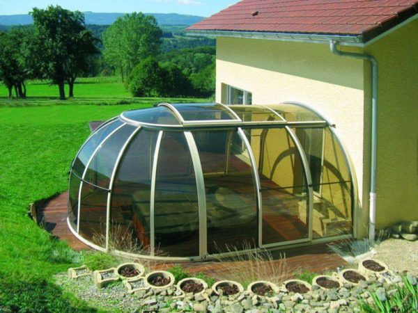 В качестве пола беседки использована пристроенная к дому терраса. Исключить перегрев на солнце благодаря тепличному эффекту позволяет сдвижной сектор крыши.