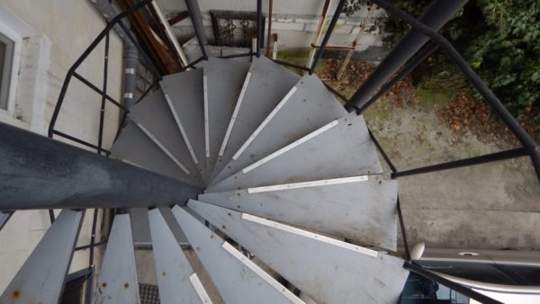 Винтовая лестница, ведущая в мансарду. Материал ступеней — фанера, покрашенная резиновой краской. Порожки на краях проступей не дают ноге соскользнуть.