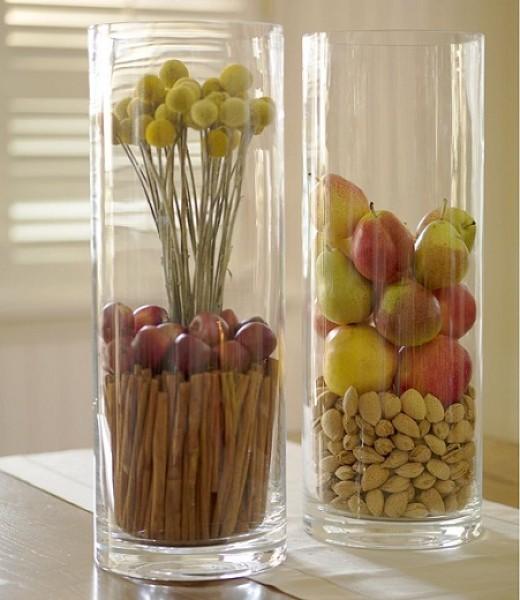 Яркие фрукты и орехи оригинально смотрятся в высокой прозрачной цветочной вазе