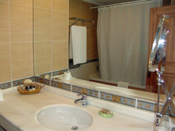 Зеркальный фартук над умывальником расширяет пространство небольшого санузла.